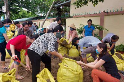 Thầy cô giáo cùng đắp bao cát làm đường đi cho học sinh